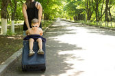 Young boy being carried on a trolley travel bag — ストック写真