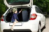 Playful boy entering the open truck of a car — Stock Photo