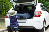 Small boy loading his suitcase — Stock Photo