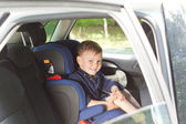 Happy little boy in a child seat — Stock Photo