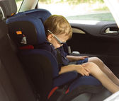 Young small boy sleeping in a child car-seat — Stok fotoğraf