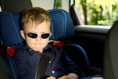 Young boy sitting in a child car-seat — Stock Photo
