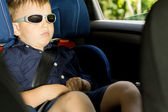 Young boy sleeping in the child car-seat — Stock Photo