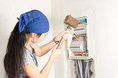 Woman taking aim at an electrical fuse box — Stock Photo