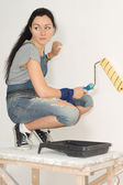 Woman painting her house with a roller — Stock Photo