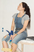 Woman sitting with a paint roller — Stock Photo