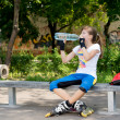Teenage roller skater pausing for a drink — Stock Photo