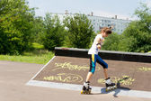 Teenage girl roller skating in a park — Stock Photo
