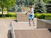 Giovane ragazza saltando in aria mentre pattinaggio — Foto Stock