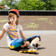 Young girl in roller blades sitting watching — Stock Photo