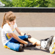 Young roller skater rubbing her calf muscle — Stock Photo #27647855