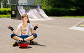 Girl in rollerblades sitting meditating — Stock Photo