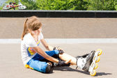 Young roller skater rubbing her calf muscle — Stock Photo