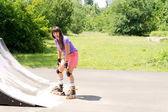 Ung flicka rullskridskoåkning på en ramp — Stockfoto