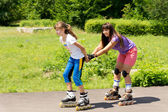 Two female friends roller skating — Stock Photo