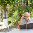 Senior man talking on mobile phone outdoors — Stock Photo