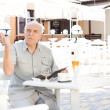 Elderly man summoning a waiter — Stock Photo