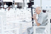 Elderly amputee sitting at a restaurant table — Stock Photo