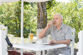 Elderly man sipping a glass of brandy — Stock Photo