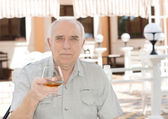 Portrait of a senior man holding a glass of brandy — Stock Photo
