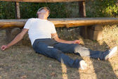 Heroin user lying down leaning on a bench — Stock Photo