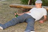 Drunk man fallen down on the ground in the park — Stock Photo