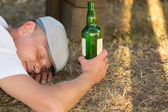 Homeless drunk adult man sleeping on the ground — Stock Photo