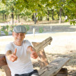 Caucasian man showing thumbs up sitting on a bench — Stock Photo