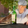 Melancholic drunk man looking at a bottle of wine — Stock Photo
