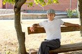 Man sitter på en bänk i en solig dag i sommar — Stockfoto