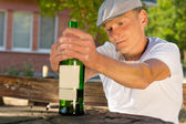 Depressed man holding a bottle of beverage — Stock Photo