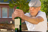 Alcoholic man feeling dizzy sitting at a table — Stock Photo