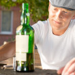 Melancholic drunk man looking at a bottle — Stock Photo