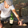 Melancholic drunk man with a bottle of white wine — Stock Photo