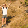Backpacker waving on a mountains slope — Stock Photo