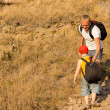 Little boy with a backpack climbing a mountain — Stok fotoğraf