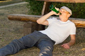 Alcoholic relaxing in a park with his liquor — Stock Photo