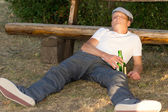 Alcoholic passed out on the ground in a park — Stock Photo