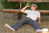Jobless adult man sitting on the ground drinking — Stock Photo
