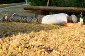 Drunk man sleeping on the ground next to a bench — Stock Photo