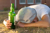 Drunk Caucasian man sleeping on the ground — Stock Photo