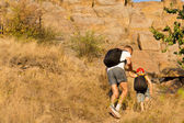 Man helping a young boy hiking on a mountain — Stock Photo