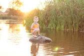 Liten pojke på en sten i sjön vid soluppgång — Stockfoto
