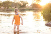 Small boy wading in a lake at sunrise — Stockfoto