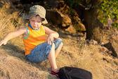 Liten pojke sitter med en ryggsäck — Stockfoto