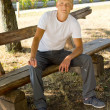 Smiling man sitting on a park bench — Stock Photo