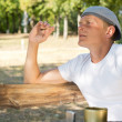 Man sitting smoking in the park — Stock Photo #31048135