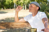 Man sitting smoking in the park — Stock Photo