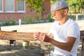 Caucasian man rolling a cigarette in a summer day — Stock Photo