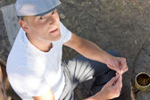 Caucasian man rolling a cigarette in the park — Stock Photo